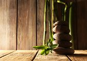 Spa stones and bamboo branches on wooden table on wooden wall background