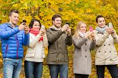 season, people, technology and friendship concept - group of smiling friends with smartphones taking picture in autumn park