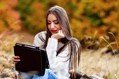 season, technology and people concept - young woman with tablet pc computer in autumn park
