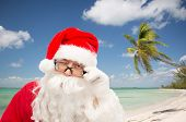 christmas, holidays, travel and people concept - close up of santa claus in glasses winking over tropical beach background