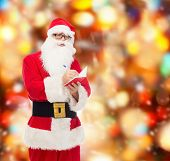 christmas, holidays and people concept - man in costume of santa claus with notepad and pen over red lights background