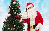 holidays, technology and people concept - man in costume of santa claus with smartphone and christmas tree over blue lights background