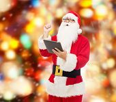 christmas, holidays, technology and people concept - man in costume of santa claus with tablet pc computer pointing finger up over red lights background