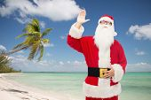 christmas, holidays, gesture, travel and people concept - man in costume of santa claus waving hand over tropical beach background