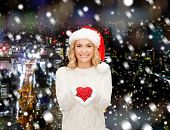 happiness, winter holidays, christmas and people concept - smiling young woman in santa helper hat with red heart decoration over snowy night city background