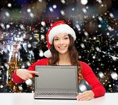 christmas, holidays, technology, advertisement and people concept - smiling woman in santa helper hat pointig finger to blank laptop computer screen over snowy night city background