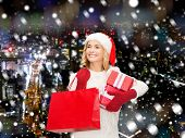 happiness, winter holidays, christmas and people concept - smiling young woman in santa helper hat with gift boxes and shopping bag over snowy night city background