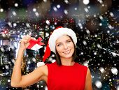 christmas, holidays, winter, happiness and people concept - smiling woman in santa helper hat with jingle bells over snowy night city background