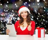 christmas, holidays, technology, gesture and people concept - smiling woman in santa helper hat with gift box and tablet pc computer showing thumbs up over snowy night city background