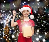 christmas, holidays, happiness and people concept - smiling girl in santa helper hat with gift box and magic wand over snowy night city background