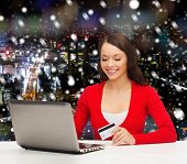 christmas, holidays, technology and shopping concept - smiling woman with credit card and laptop computer over snowy night city background