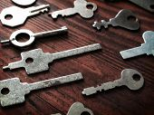 Distinctive keys. Many odd shaped keys on old wood table . Security and encryption, concept image.