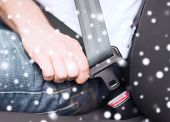 transportation, safety, people and vehicle concept - close up of man fastening seat belt in car