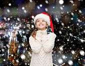 christmas, holidays, childhood and people concept - smiling girl in santa helper hat over snowy night city background