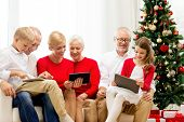 family, holidays, christmas, technology and people concept - smiling family with tablet pc computers sitting on couch at home