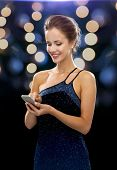 technology, communication, holidays and people concept - smiling woman in evening dress holding smartphone over night lights background