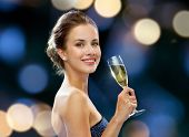 party, drinks, holidays, luxury and celebration concept - smiling woman in evening dress with glass of sparkling wine over night lights background