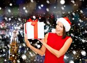 christmas, holidays, celebration and people concept - smiling woman in red dress with gift box over background