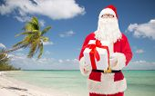 christmas, holidays, travel and people concept - man in costume of santa claus with gift box over tropical beach background