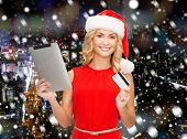 christmas, technology, shopping and people concept - smiling woman in santa helper hat with tablet pc computer and credit card over snowy night city background