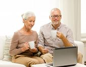 family, technology, drinks, age and people concept - happy senior couple with laptop computer and cups at home