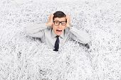 Terrified man panicking in a pile of shredded paper