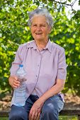 Senior woman drinking water in the orchard