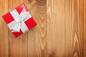 Red gift box over wooden background with copy space