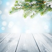 Christmas winter background with snow fir tree, wooden table and blurred bokeh
