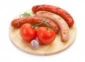 Various grilled sausages with condiments and tomatoes on cutting board. Isolated on white background