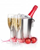 Champagne bottle in ice bucket, two glasses and christmas decor. Isolated on white background