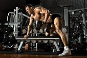 picture of execution  - very power athletic guy execute exercise with dumbbells on broadest muscle of back - JPG