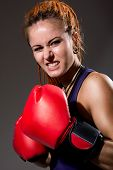 Beautiful Girl With Red Boxing Gloves, Aggressive And Looking At The Camera