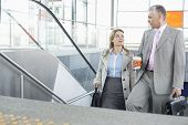 Businessman conversing with female colleague while walking up stairs in train station