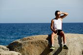 Exhausted runner after workout resting seated on big rocks