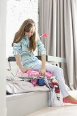 Full-length of girl trying to close suitcase at home