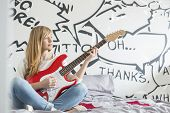 Full-length of teenage girl playing guitar in bedroom