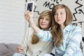 Cute sisters taking photos with smart phone at home