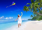 Woman flying a kite on the beach.
