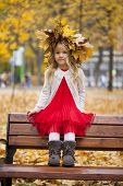 Beautiful little girl sitting on a bench in autumn park