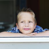 little boy pondering in window sill