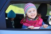 Portrait of happy little girl in striped hat looking out car window