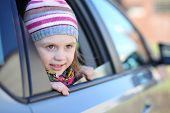 Portrait of little girl in striped hat looking out car window