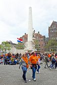 AMSTERDAM - APRIL 26: On the Dam square people in orange celebrating kings day on April 26, 2014 in Amsterdam, The Netherlands