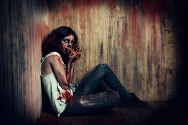 foto of doomsday  - Terrible bloody zombie chews the bones of her victims - JPG