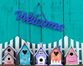 picture of bird fence  - Purple welcome sign hanging over white picket fence with row of colorful birdhouses with antique teal blue wooden background - JPG