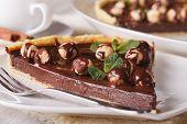 stock photo of tarts  - A piece of chocolate tart with hazelnut on a table macro - JPG