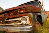 picture of yesteryear  - Extreme closeup of an old vintage truck rusting away in a grassy field - JPG