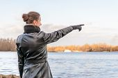 picture of indications  - An adult with a chignon and wearing a black leather coat stays close to the river and point her finger to indicate something interesting on the opposite bank  - JPG
