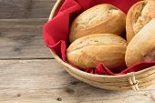 picture of bread rolls  - bread rolls in a basket whith red napkin on a table from old wood - JPG
